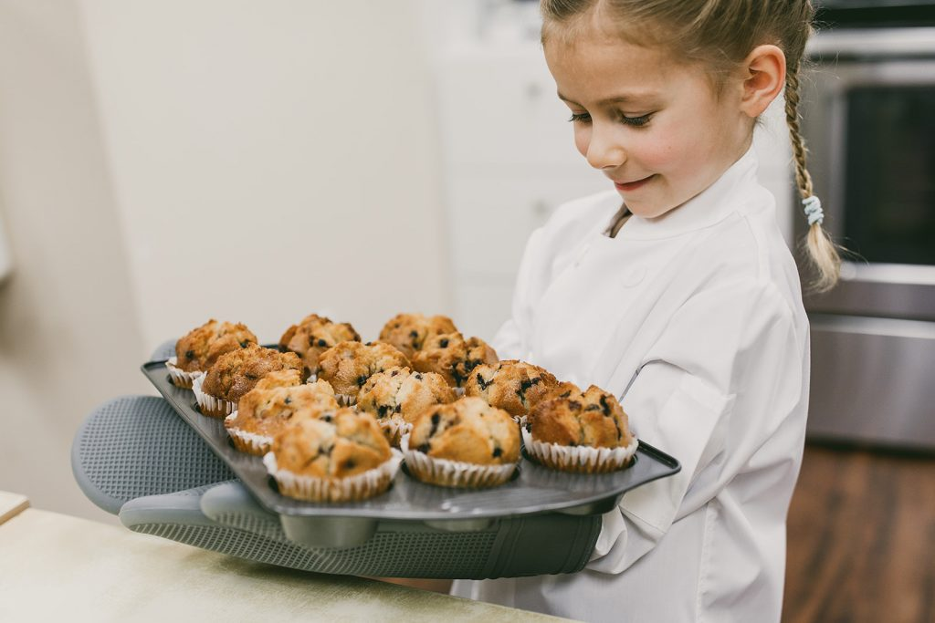 girl carrying blueberry muffins