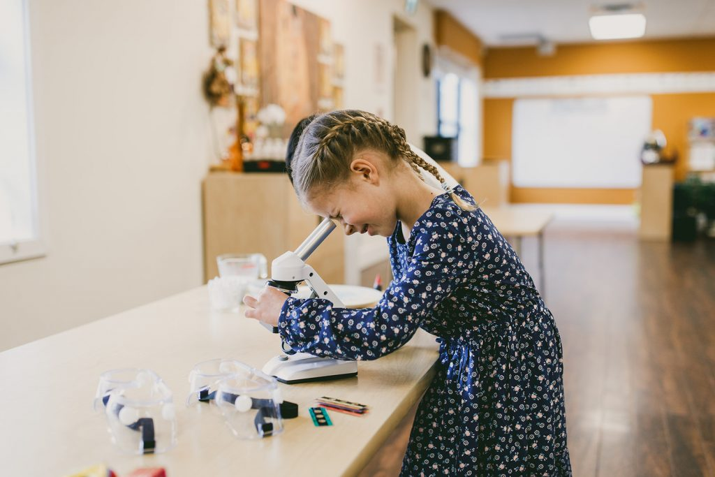 Girl looking through a microscope