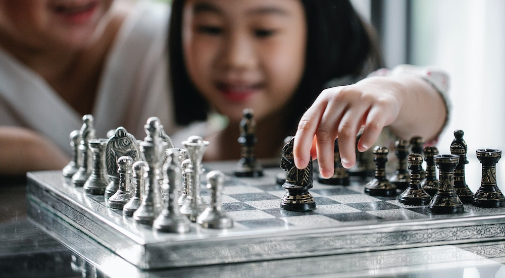 girl playing chess at Enrichment Programs
